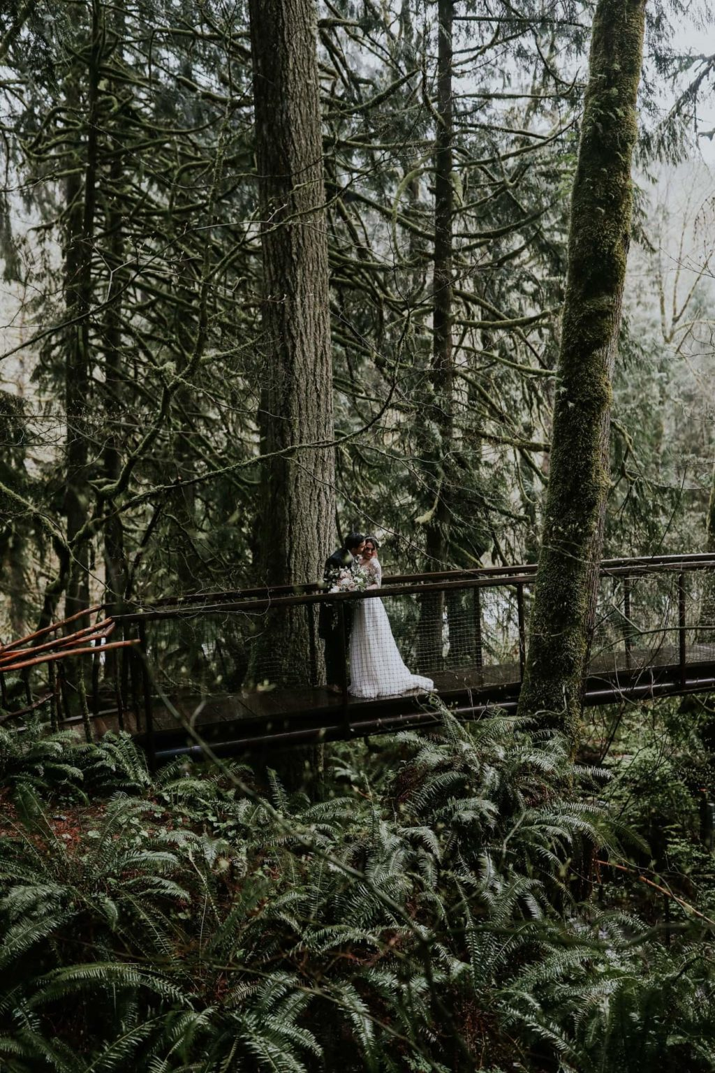 Bride and groom kissing on woodsy bridge
