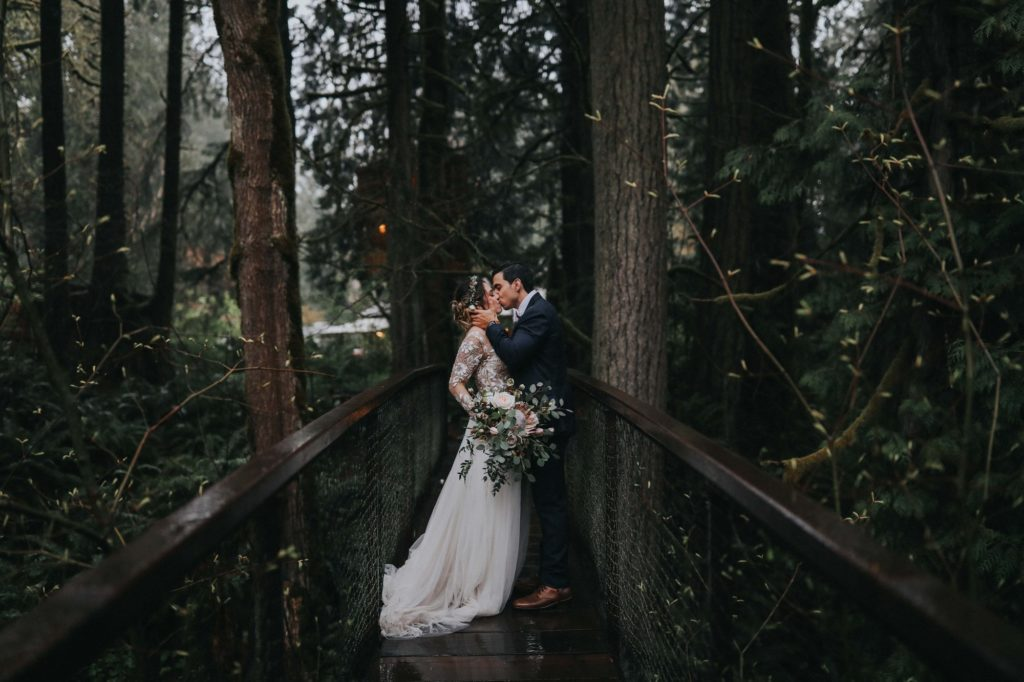 Bride and Groom kissing on suspension bridge at Treehouse Point wedding