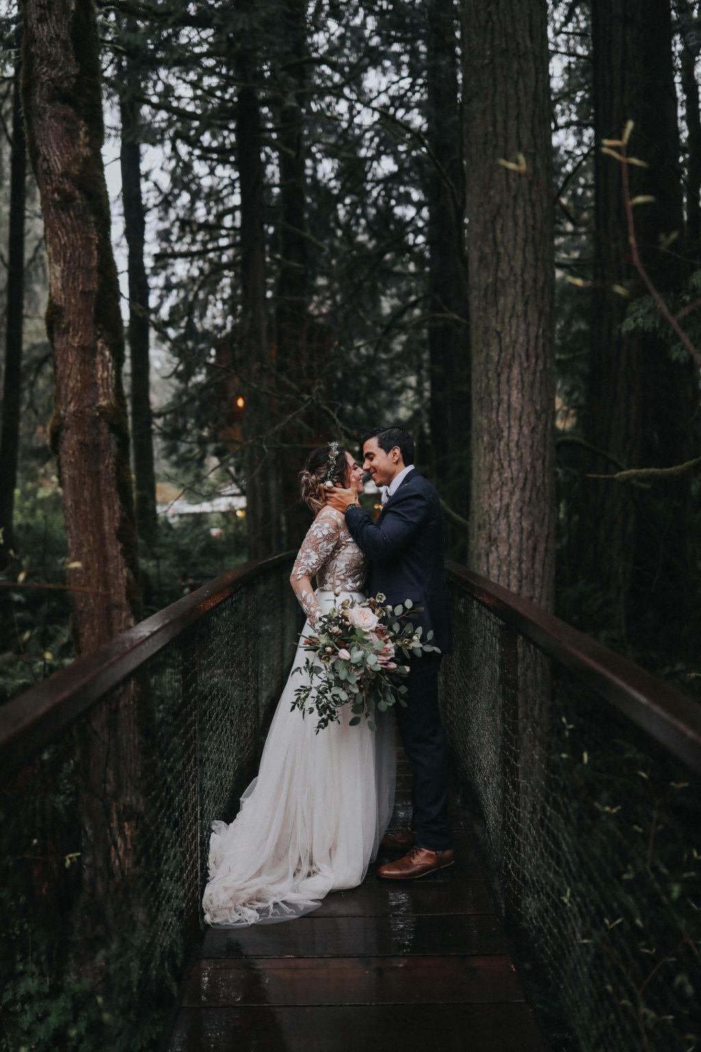 bride and groom kissing on suspension bridge