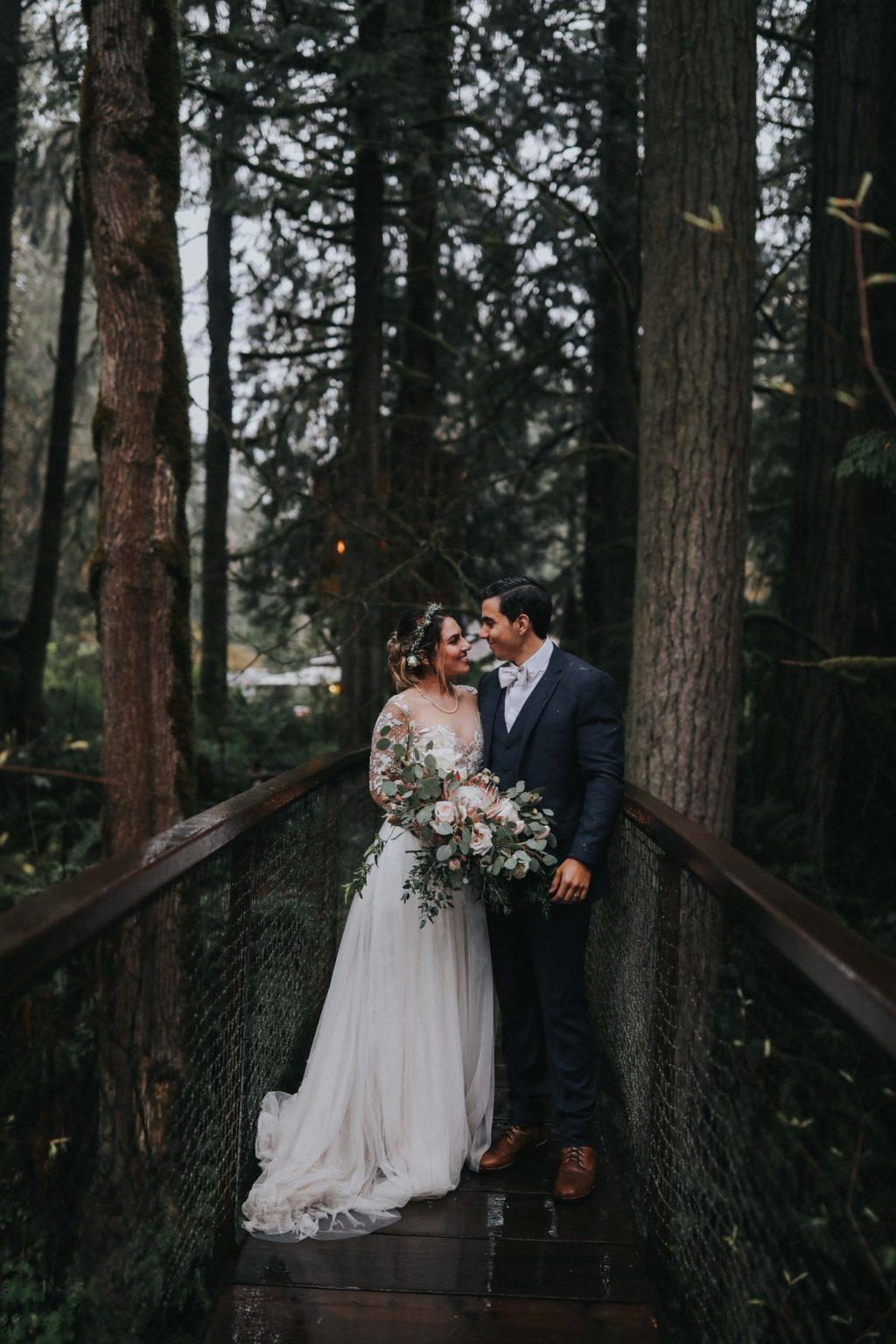 bride and groom smiling on suspension bridge