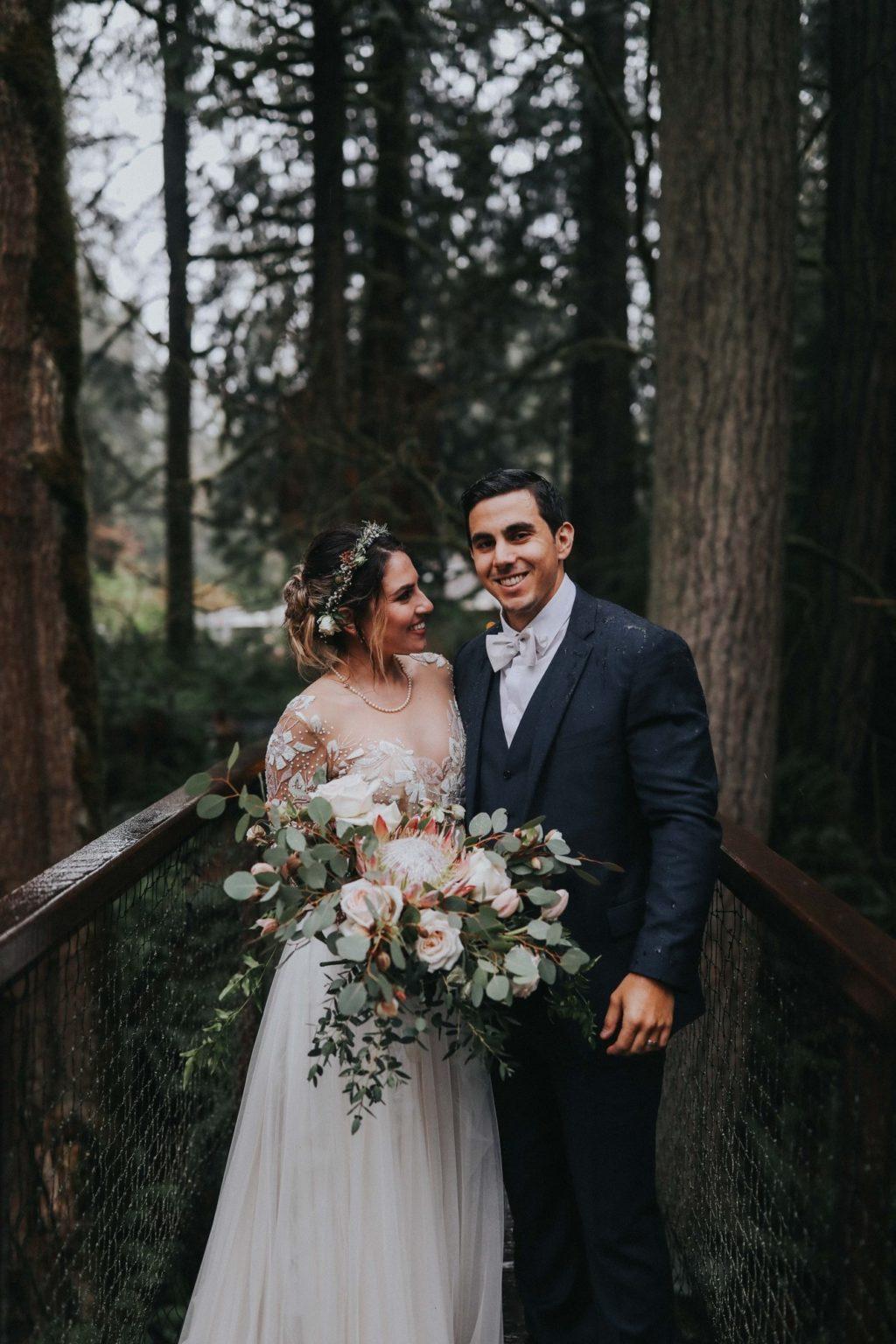 bride looking at groom while groom smiles on treehouse point wedding venue bridge