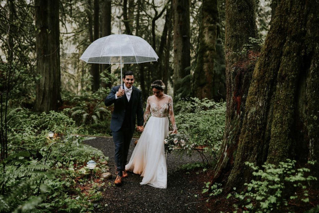 Bride and groom walking with clear umbrella in the rainy