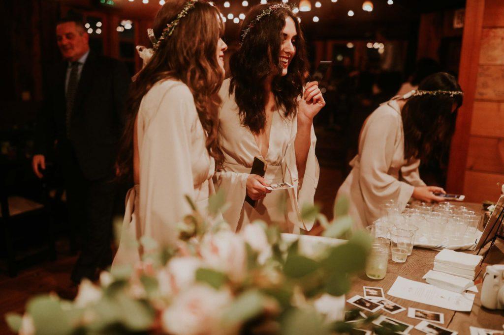 bridesmaids laughing and taking polaroids