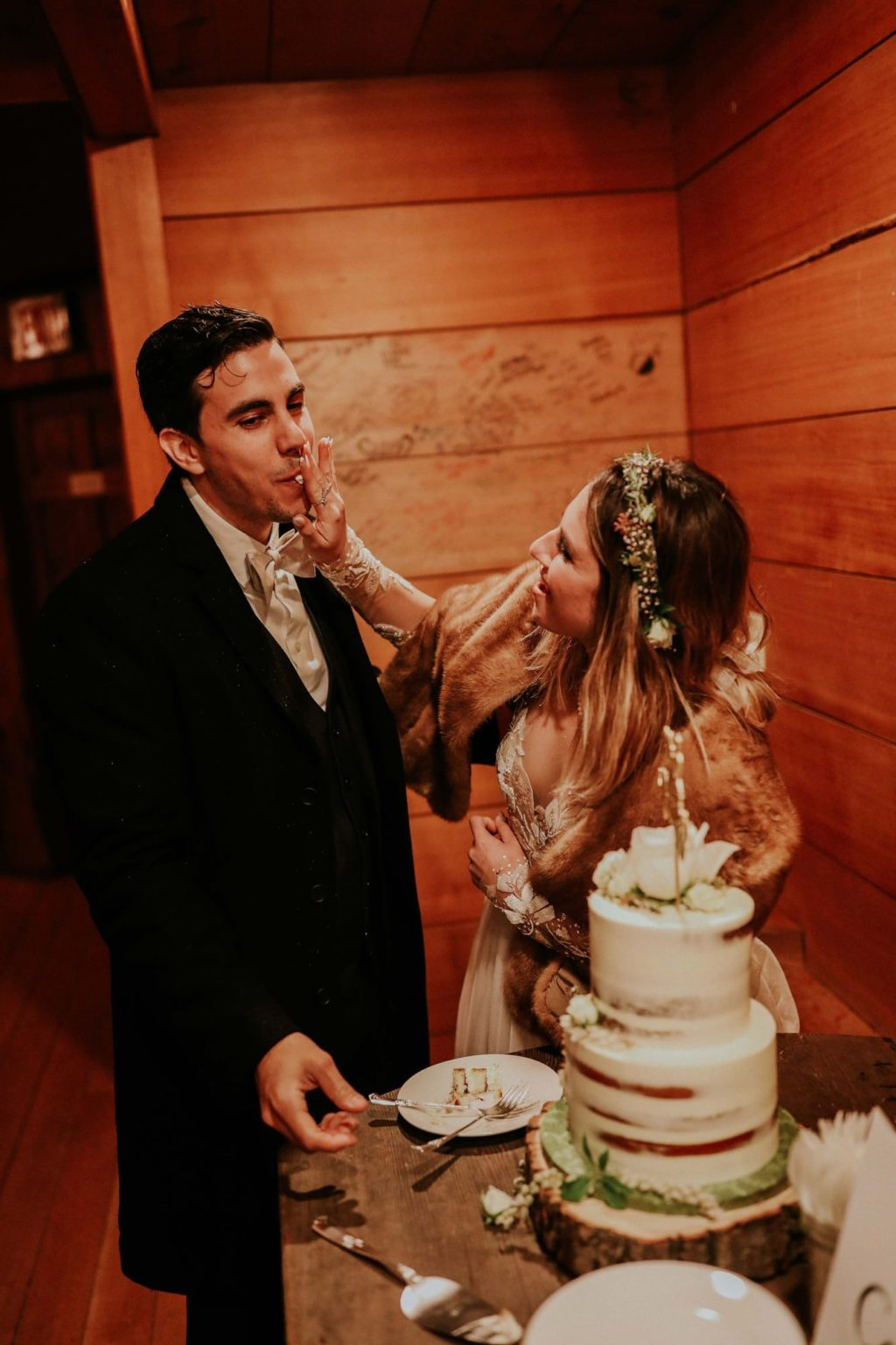 bride wiping cake off groom's face