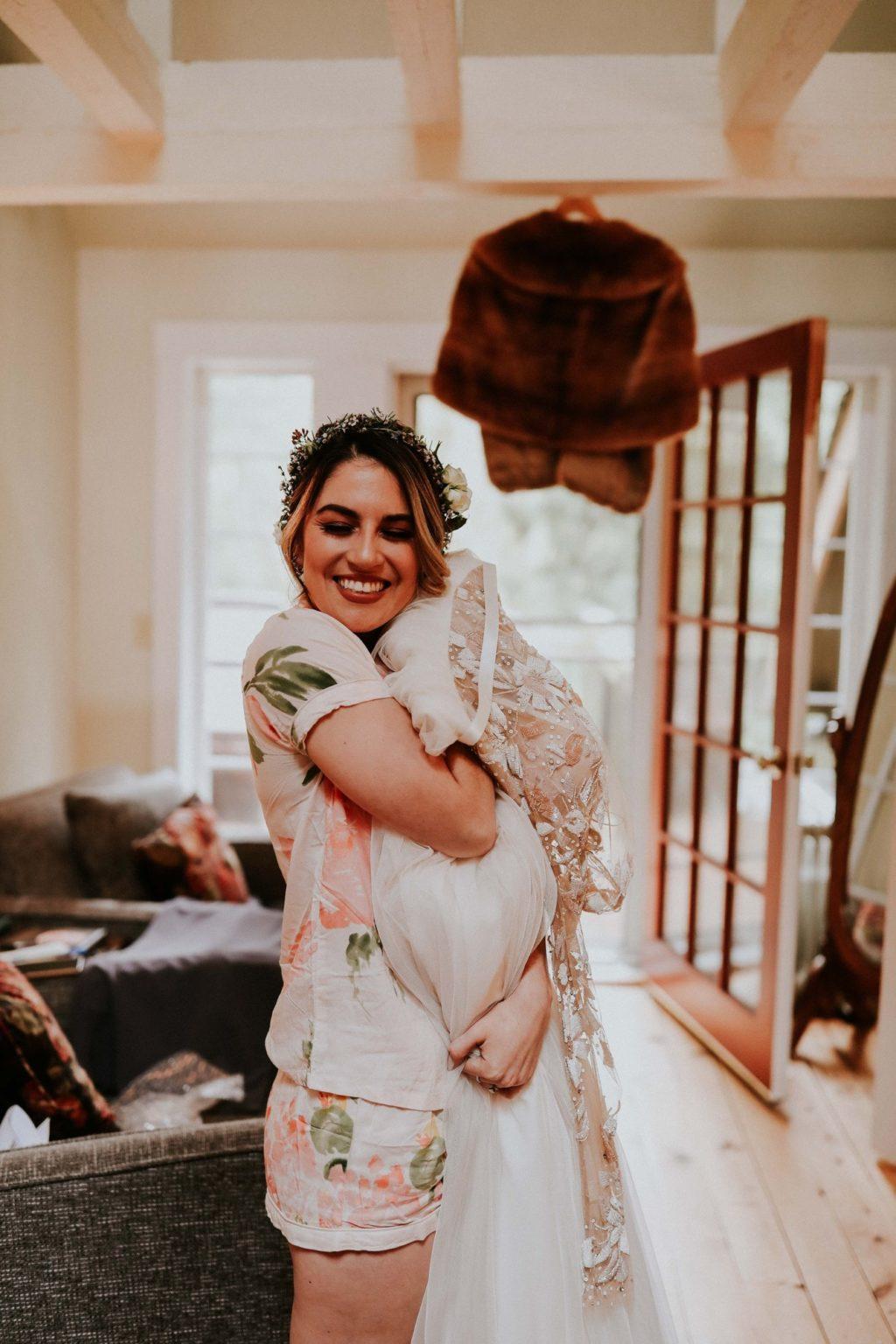 boho bride hugging her hayley paige wedding dress