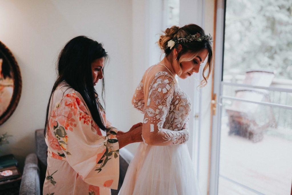 mom helping bride put on her hayley paige wedding dress