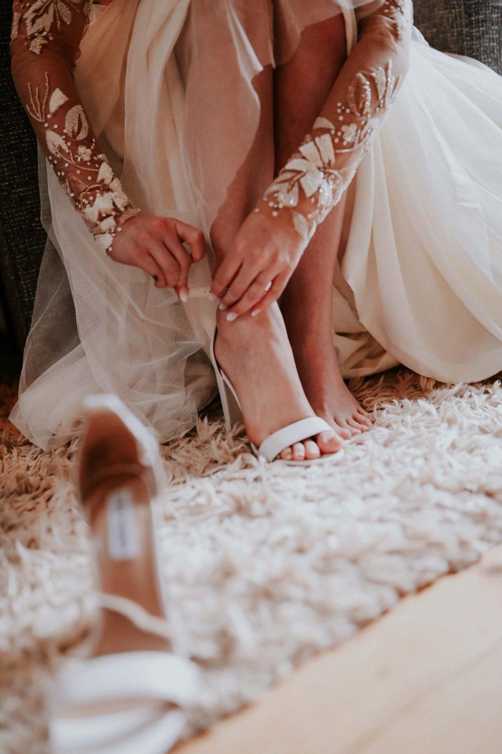 boho bride putting shoes on