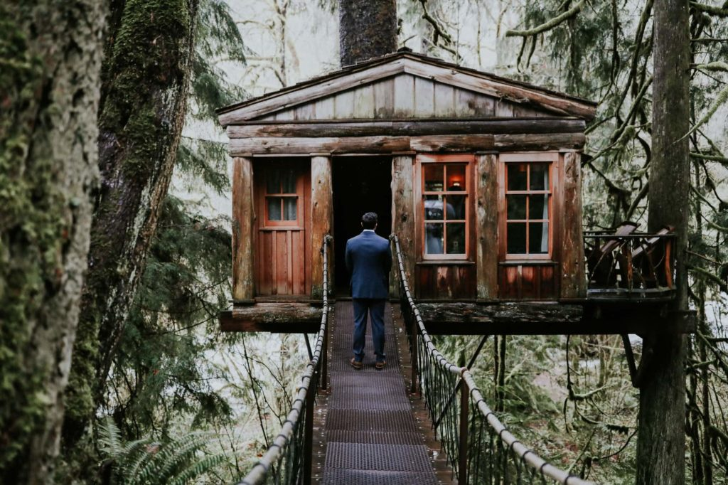 groom waiting outside his treehouse at his treehouse point wedding