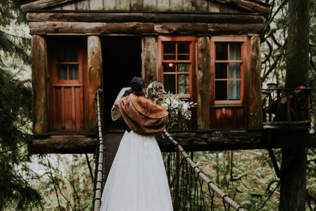 bride and groom hugging at their rainy treehouse point wedding