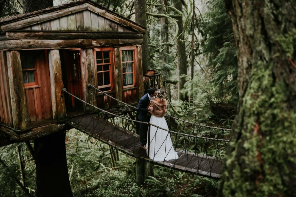 Bride and groom kissing at the treehouse point wedding venue