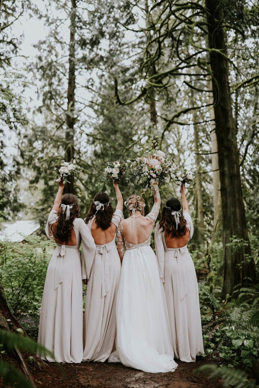 bridesmaids raising their bouquets at treehouse point wedding