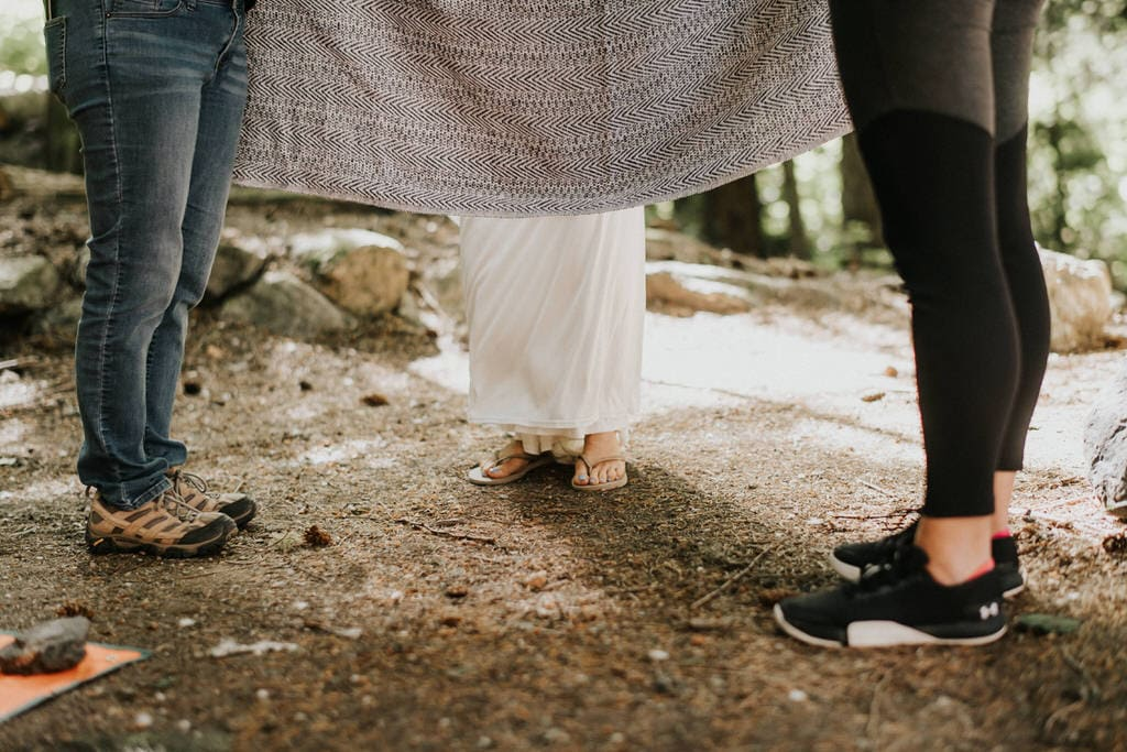 bride getting dressed at campsite