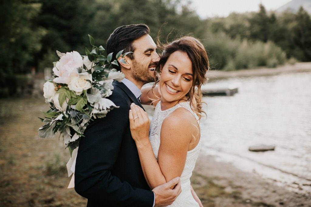 groom whispering into brides ear at diablo lake washington
