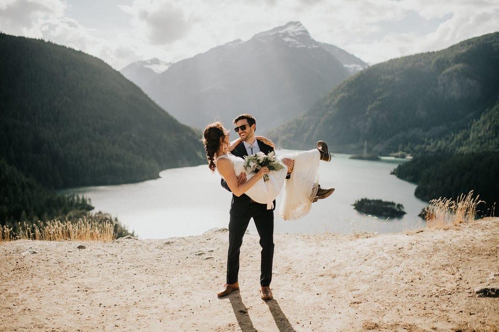 groom sweeping bride offer feet