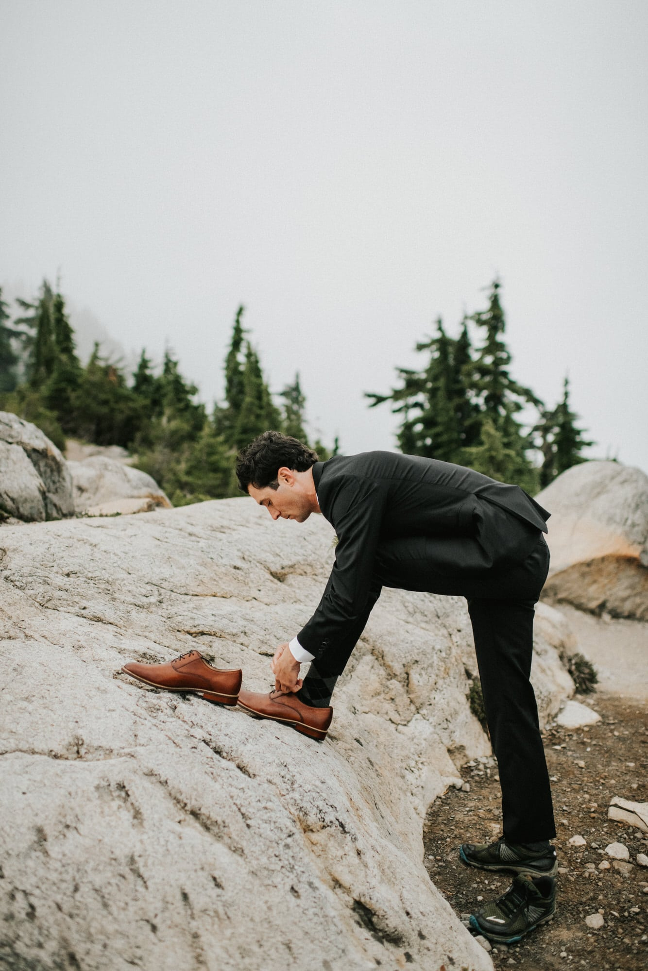 groom putting on shoes for mountaintop intimate wedding