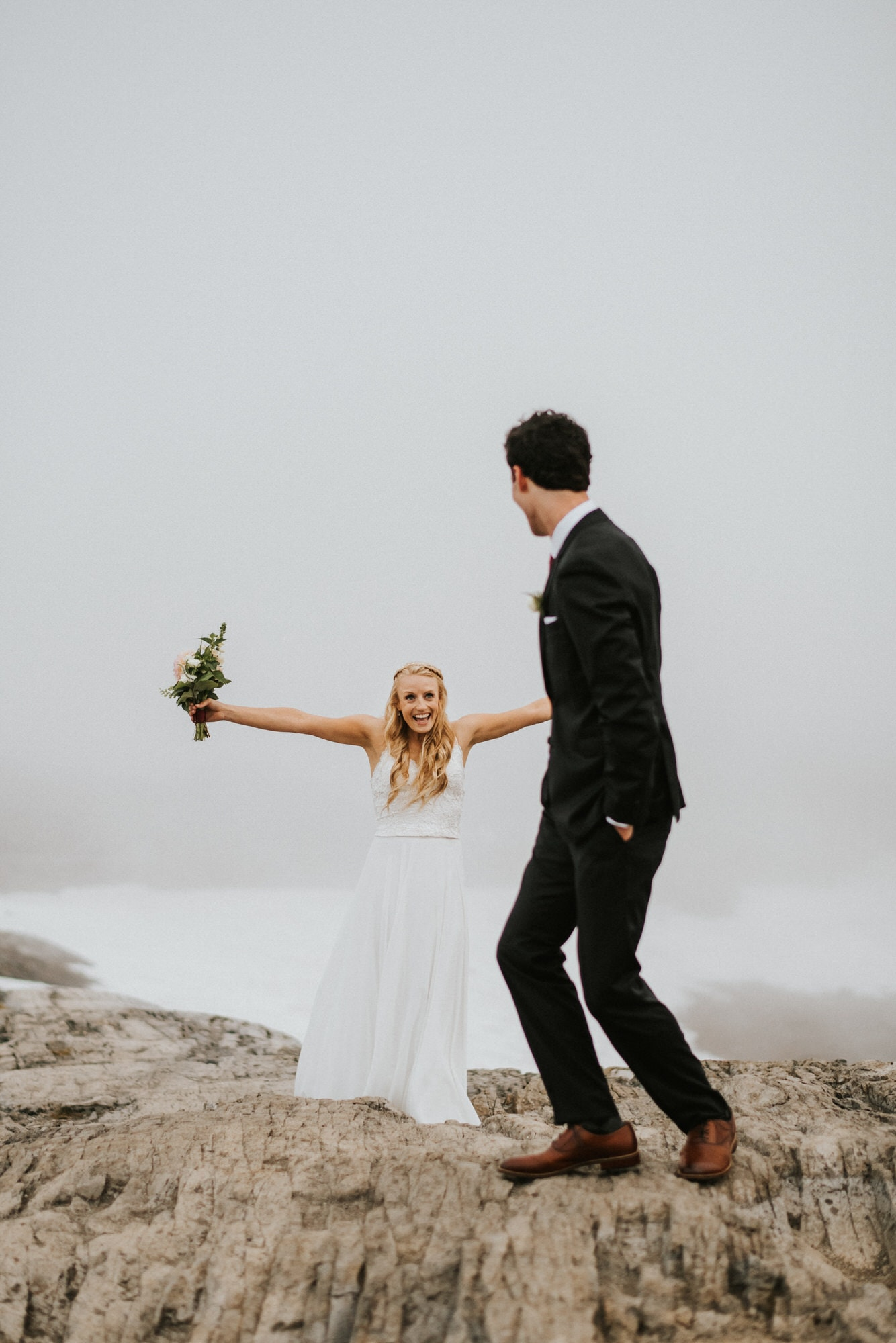 bride excited to see groom for the first time on a mountain in washington