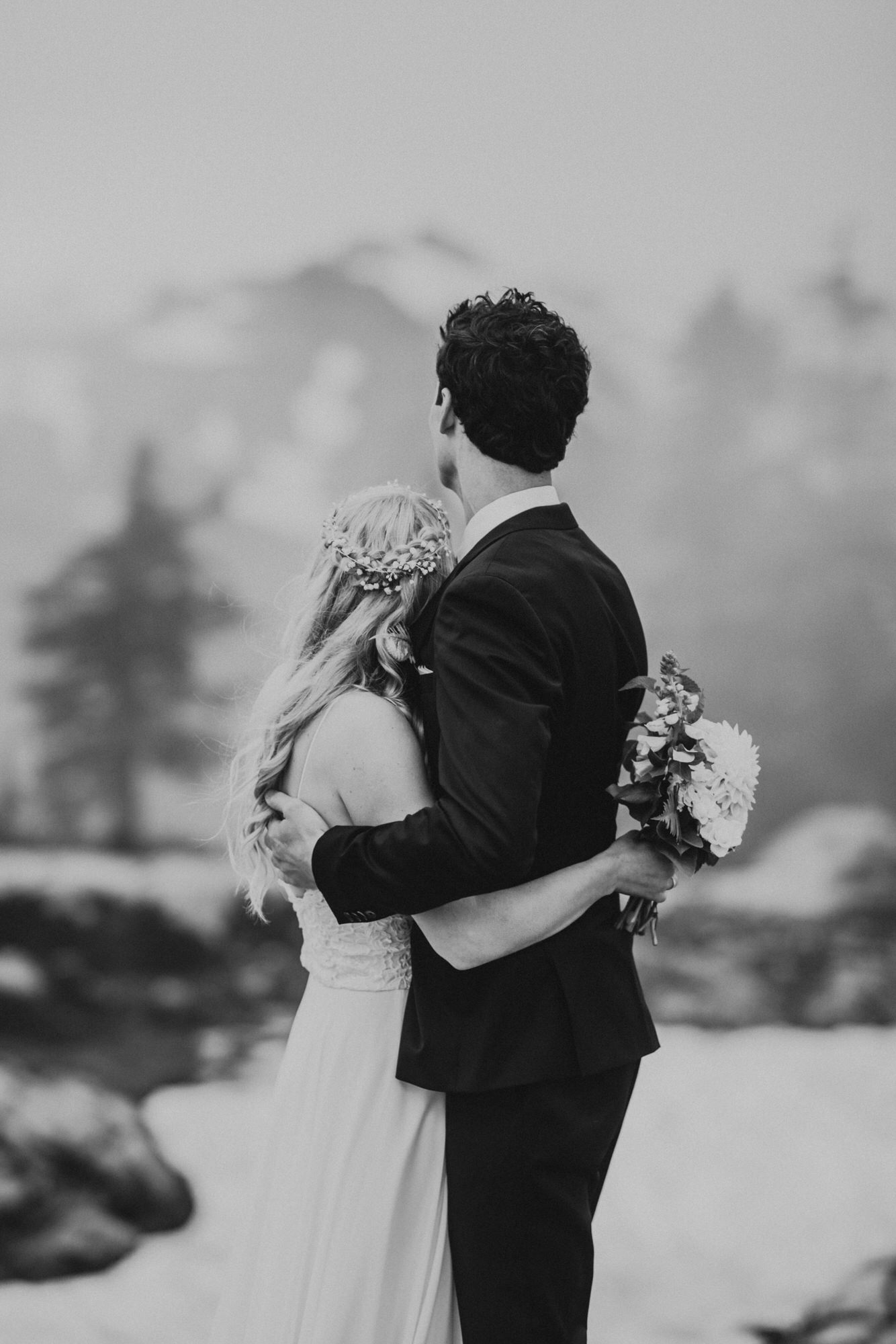 bride and groom holding each other in the fog