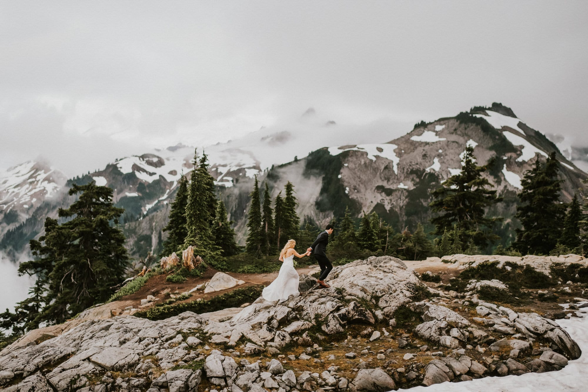 bride and groom hiking on a mountain together artist point