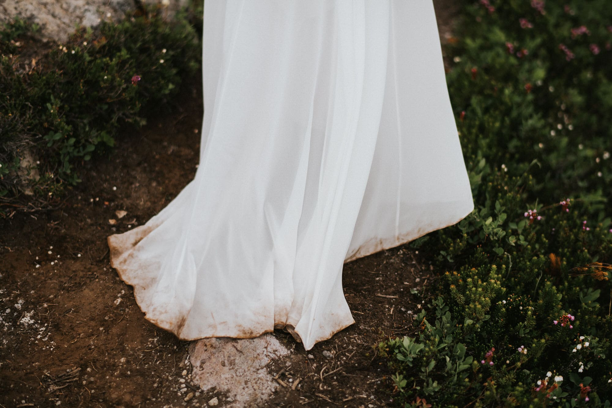 bride hiking with dirty dress