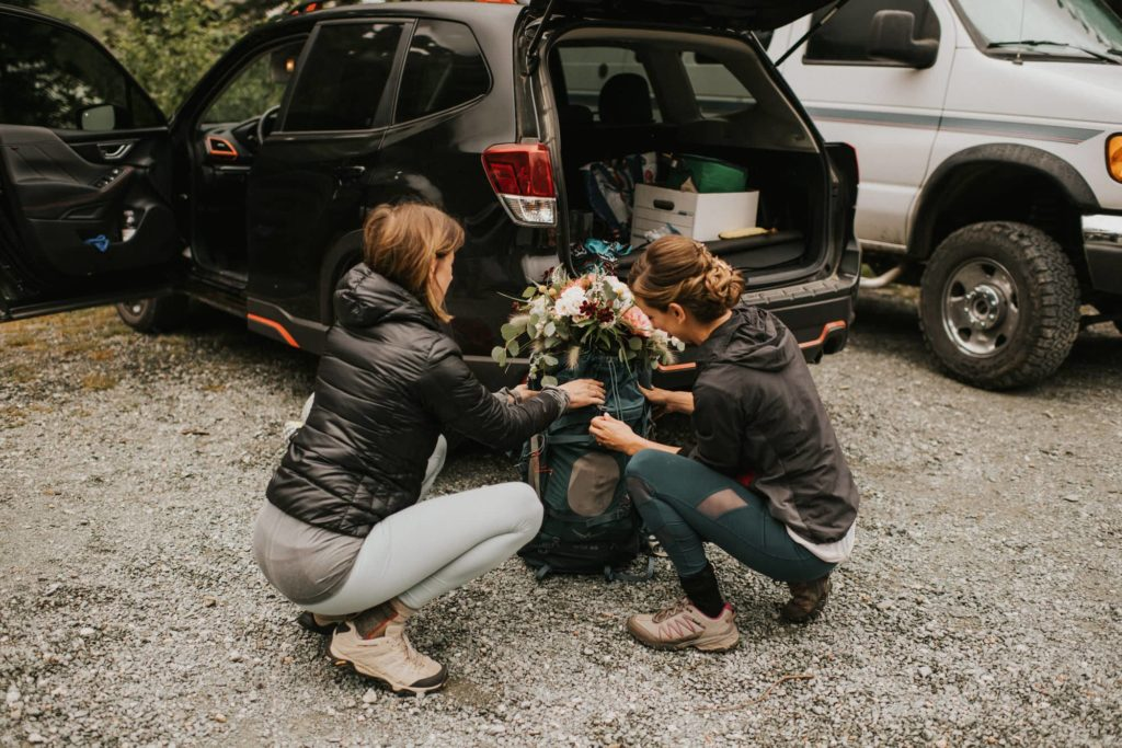 bride placing her bouquet into her backpack for her adventure wedding