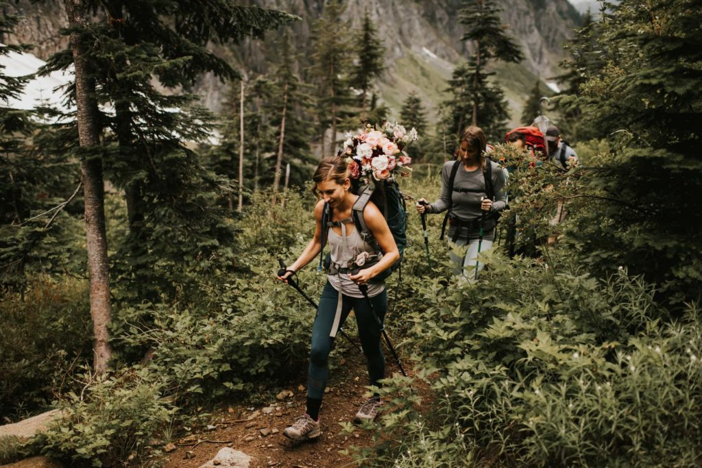 bride hiking with hiking poles on her wedding day