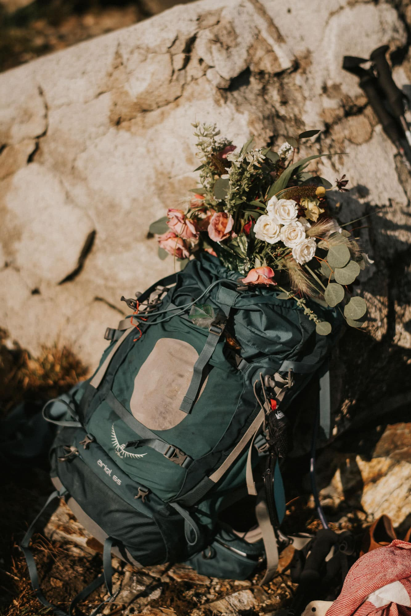 brides bouquet secured in her backpack for her elopement