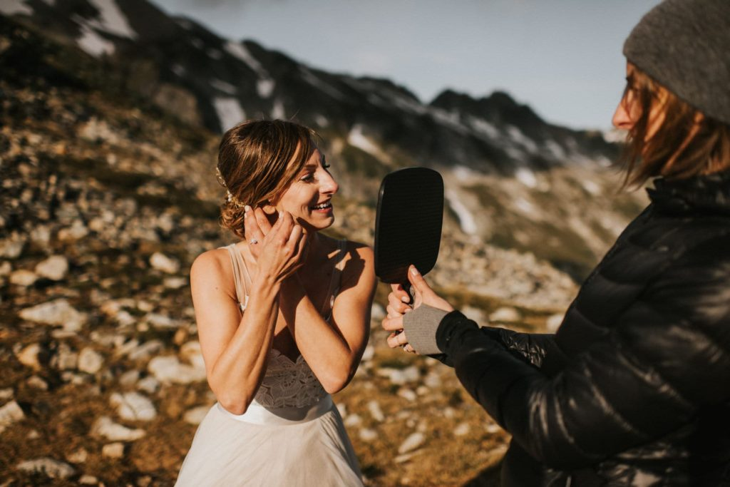 bride putting on her earrings on the top of a mountain