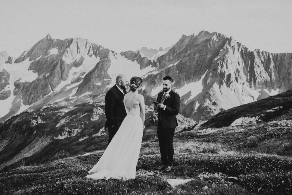 Groom reading wedding vows during north cascades adventure wedding