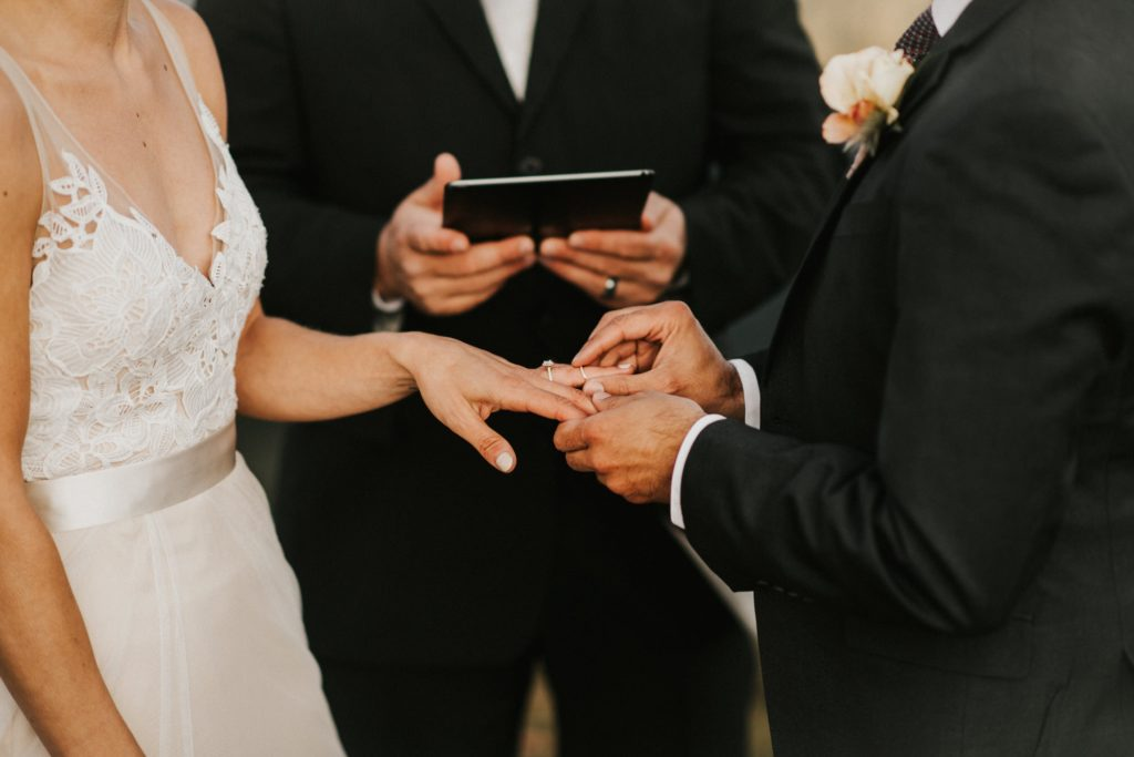 groom putting wedding ring on the brides finger
