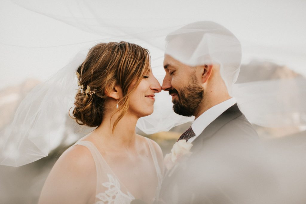 bride and groom under veil at adventure wedding