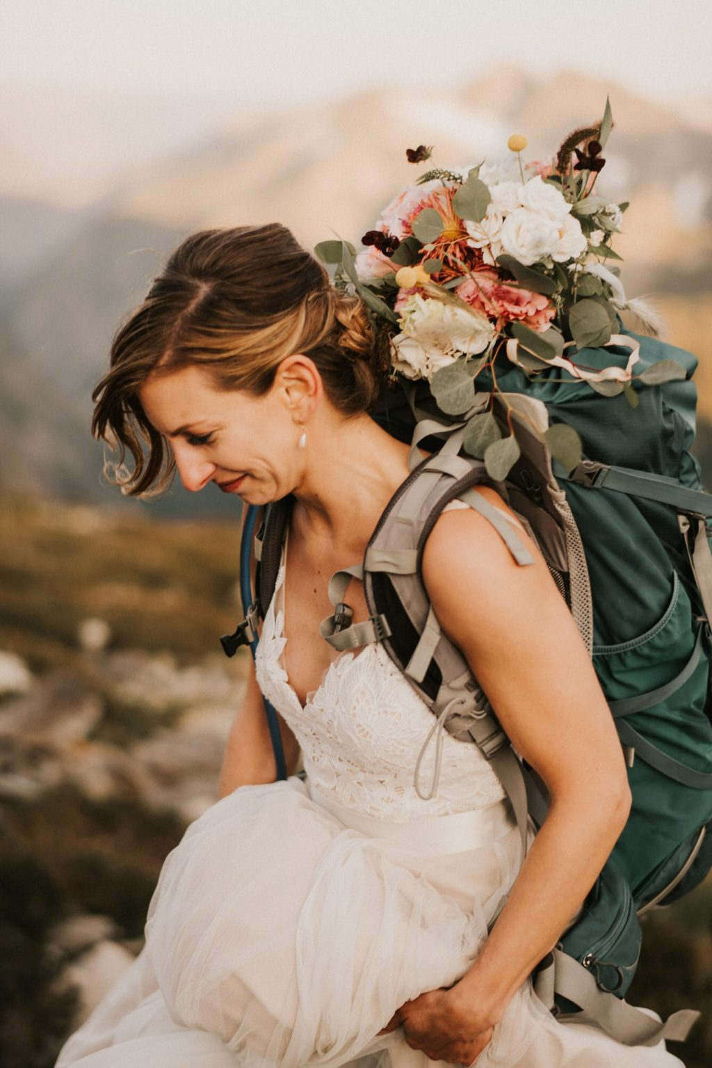 Bride with backpack going hiking in the mountains
