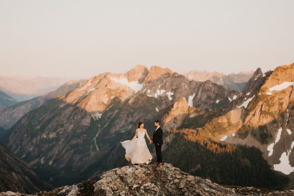 bride and groom holding hands in the mountains