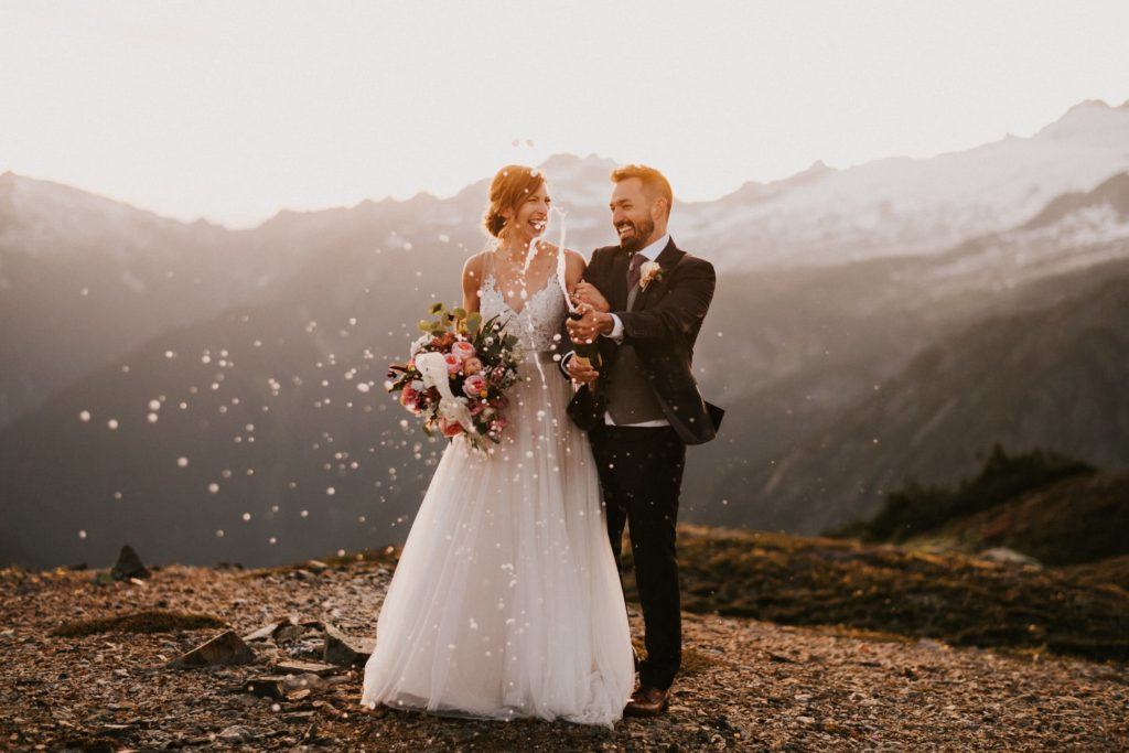 bride and groom spraying champagne after their north cascades adventure wedding