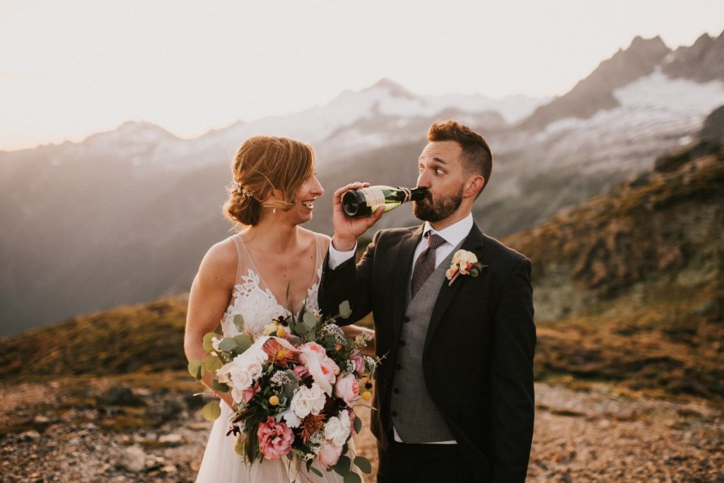 Popping a bottle of Champagne after their North Cascades Adventure Wedding