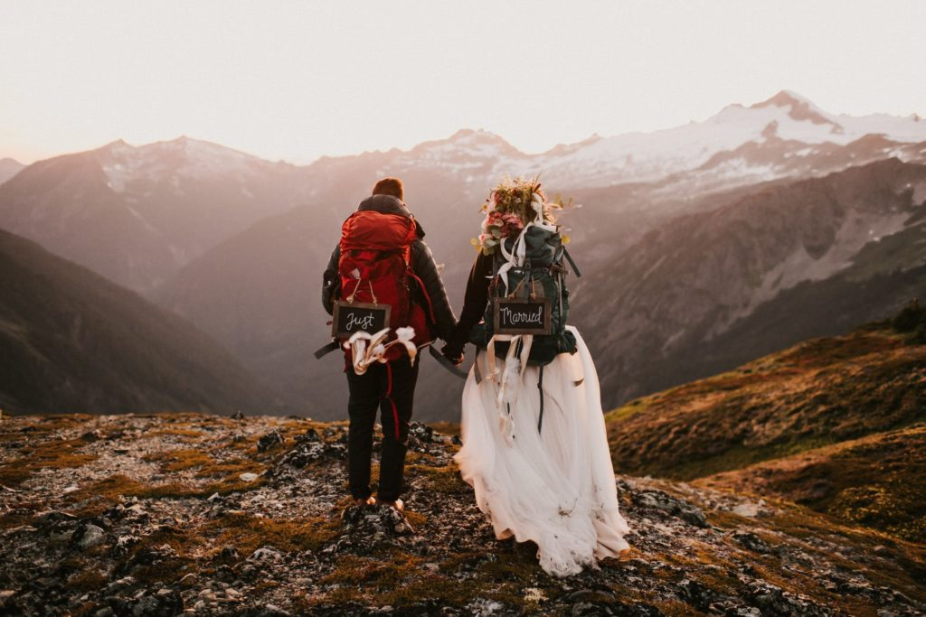 Bride and Groom holding hands watching the sunset during their north cascades adventure wedding