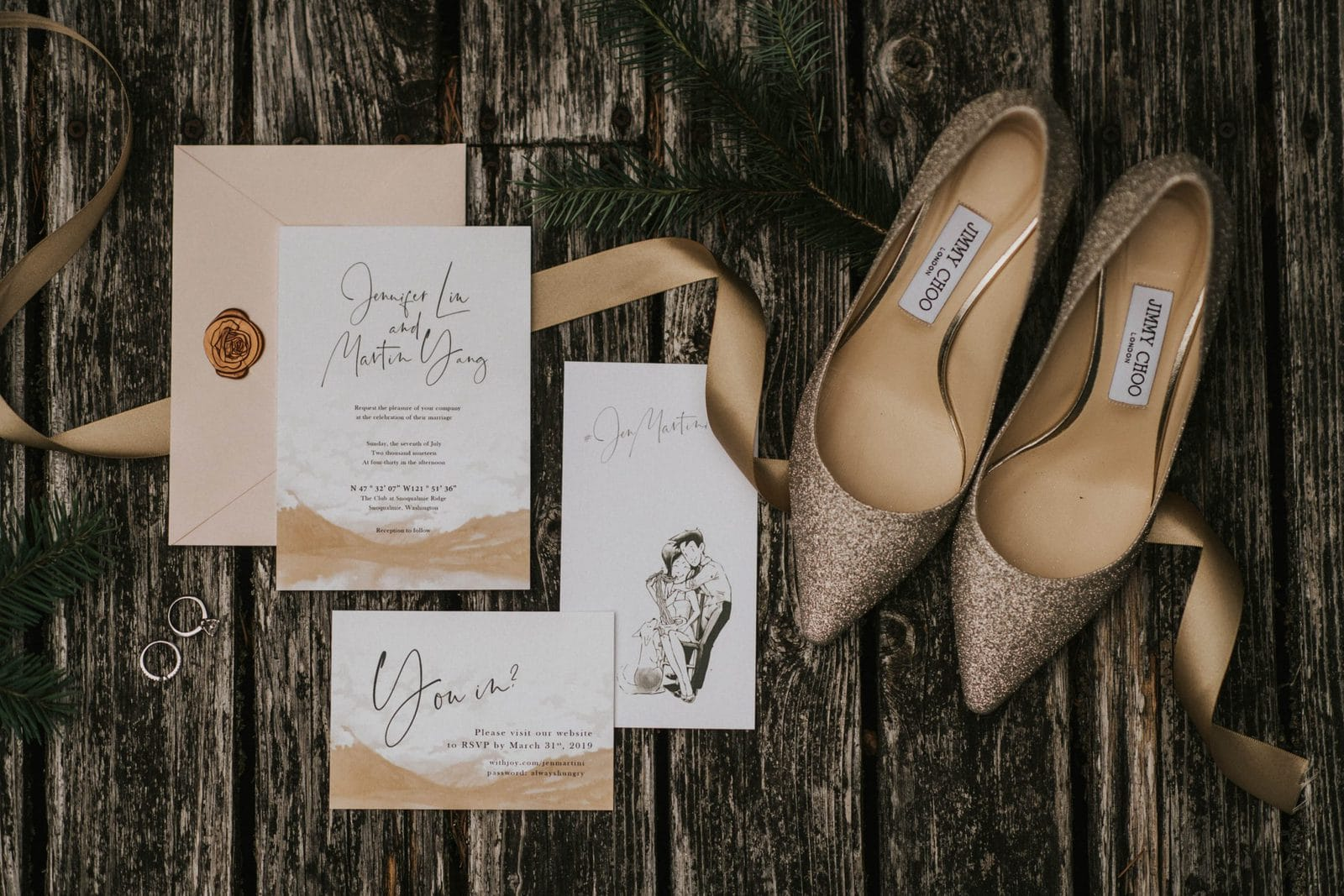 Wedding details: shoes, invitations and rings on wood floor