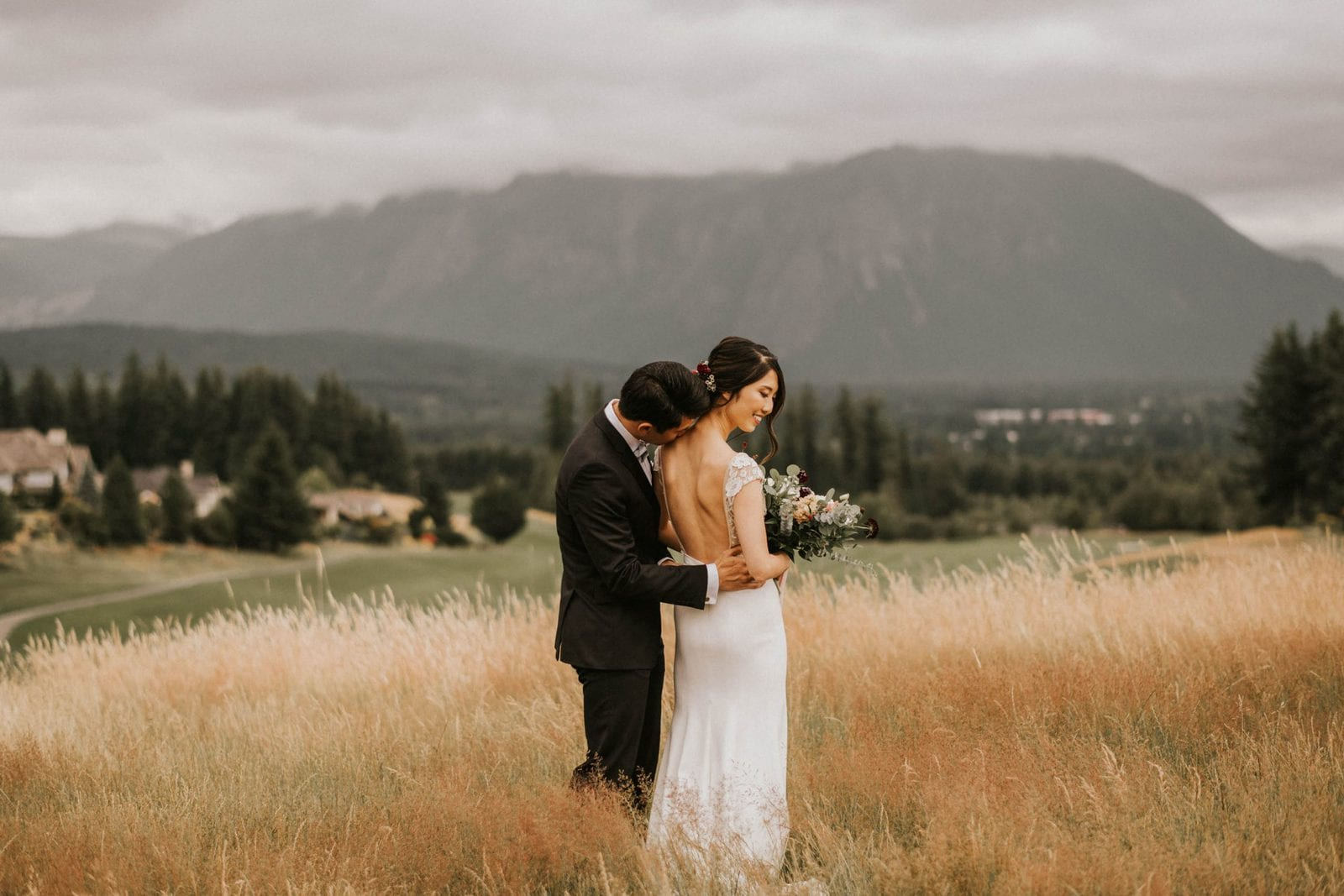 Bride and groom posing in open field with mountains in the background