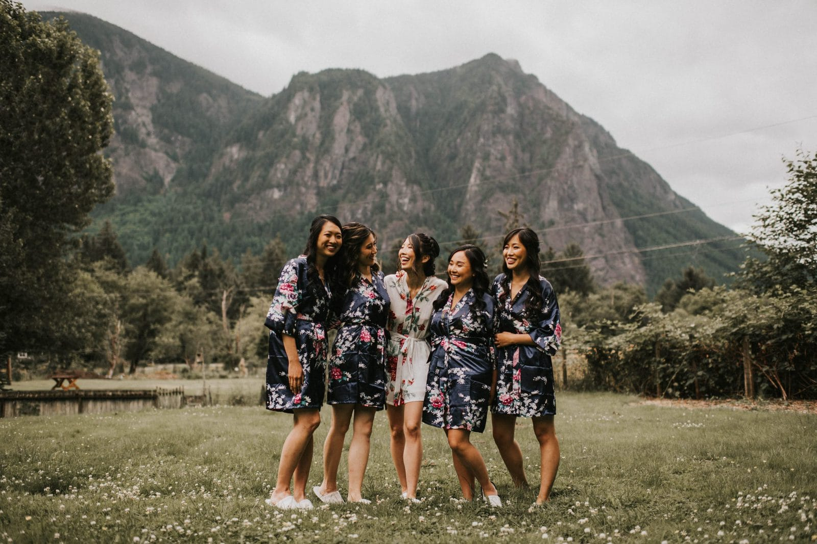 bridesmaids posing in front of mountains wearing robes