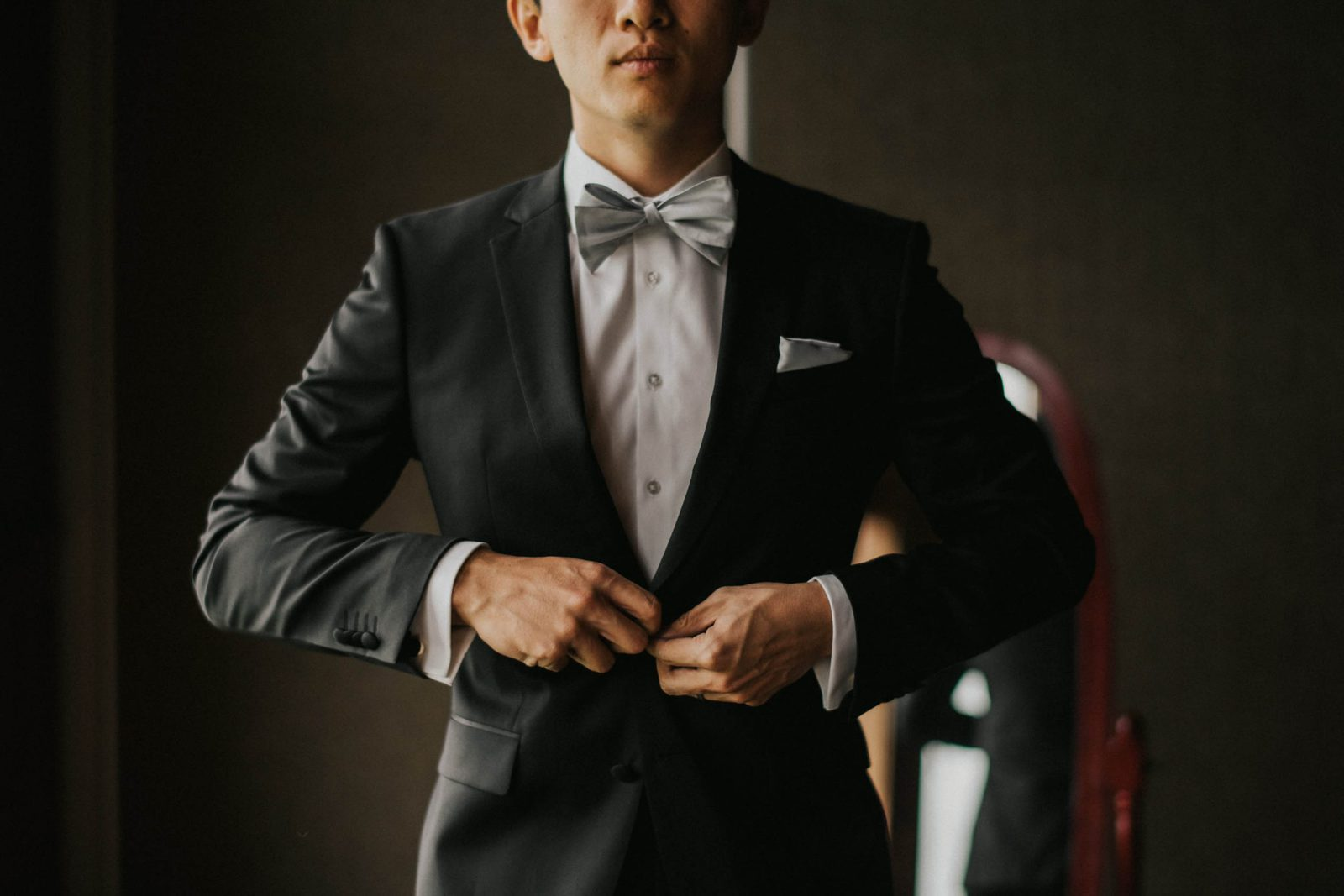 groom buttoning his tux