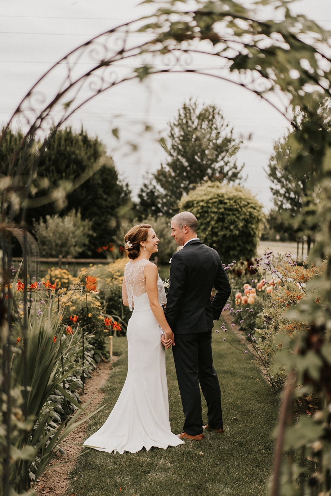 bride and groom taking photos in garden of flowers