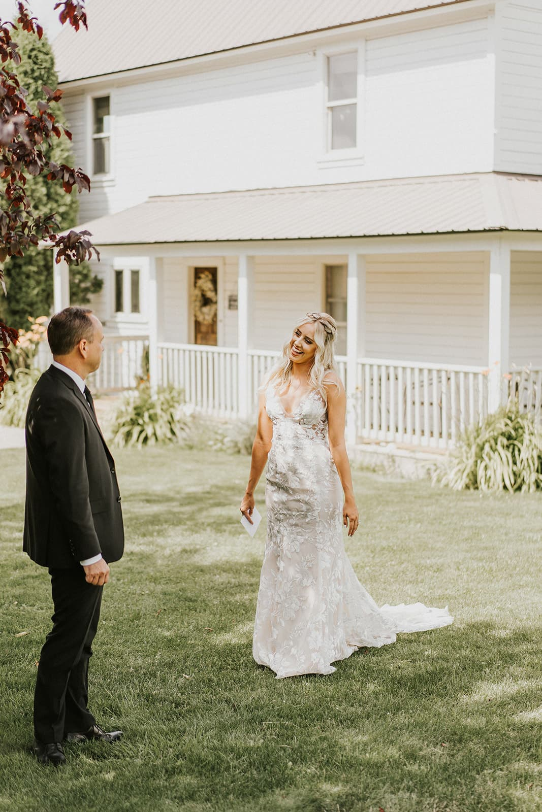 brides emotional first look with dad in from of white farmhouse