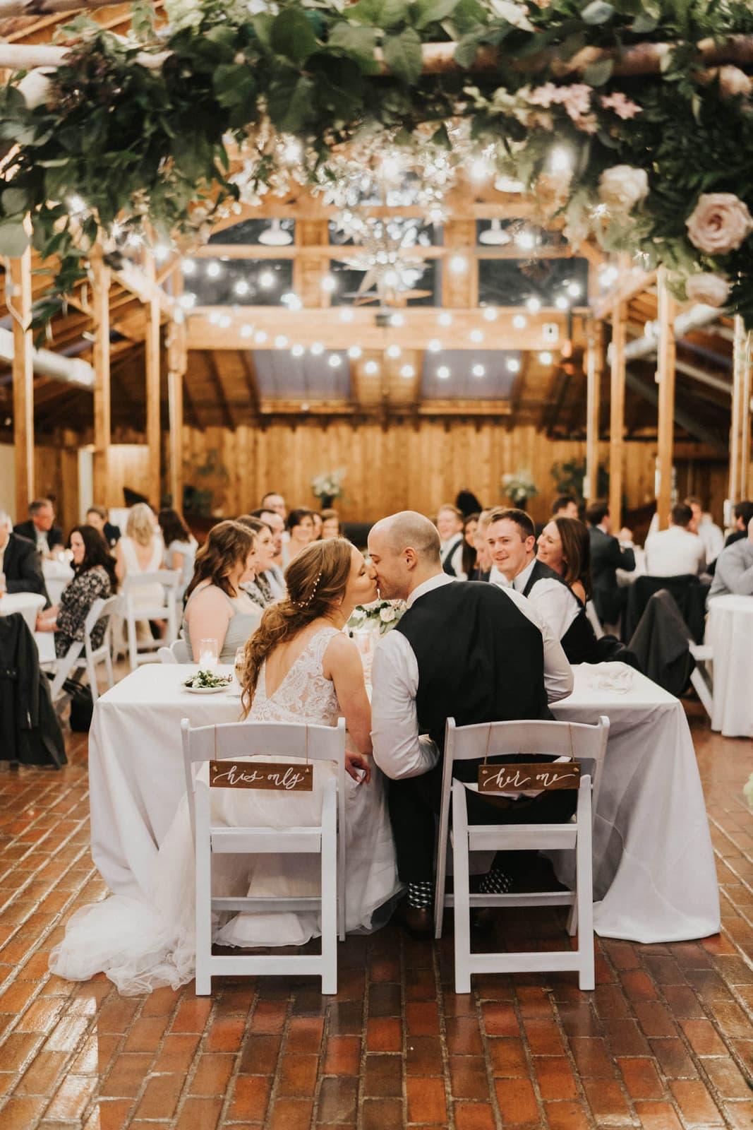 bride at groom kissing at head table kiana lodge wedding