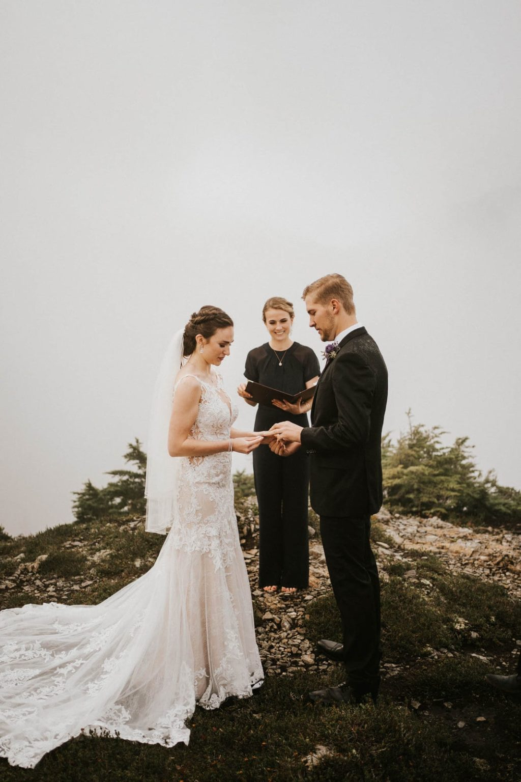 bride putting on grooms ring