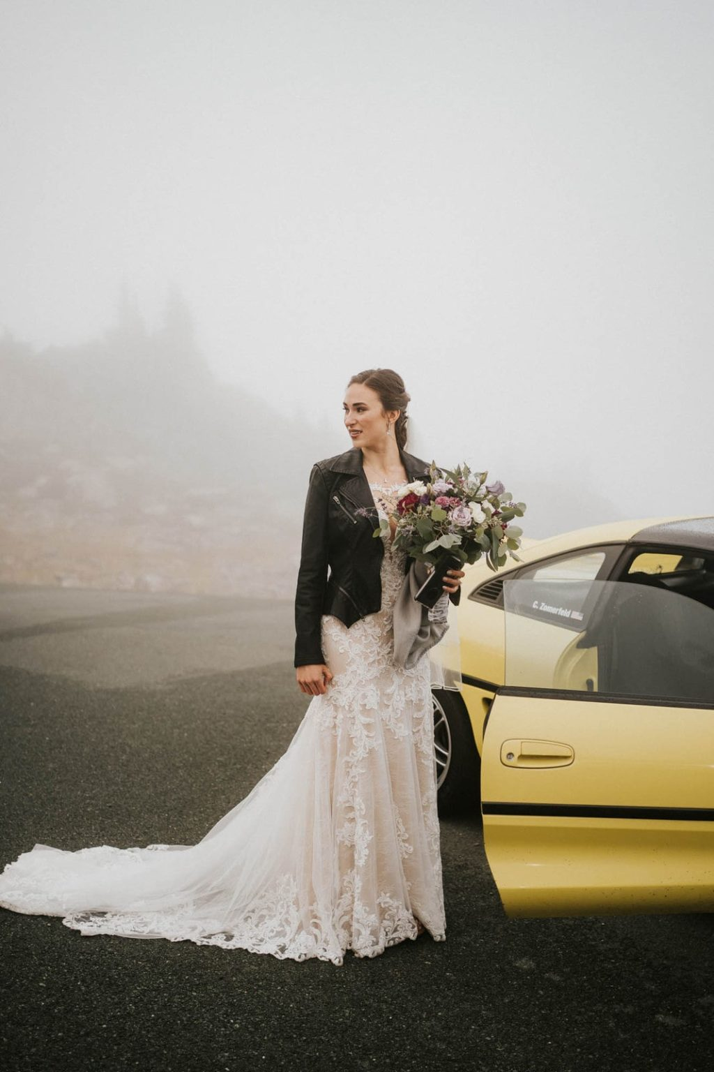 bride standing in front of car with a leather jacket on