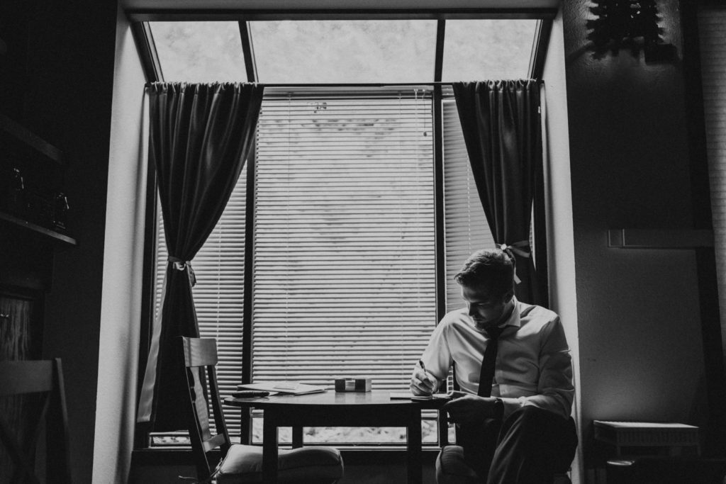 Groom writing vows in black and white
