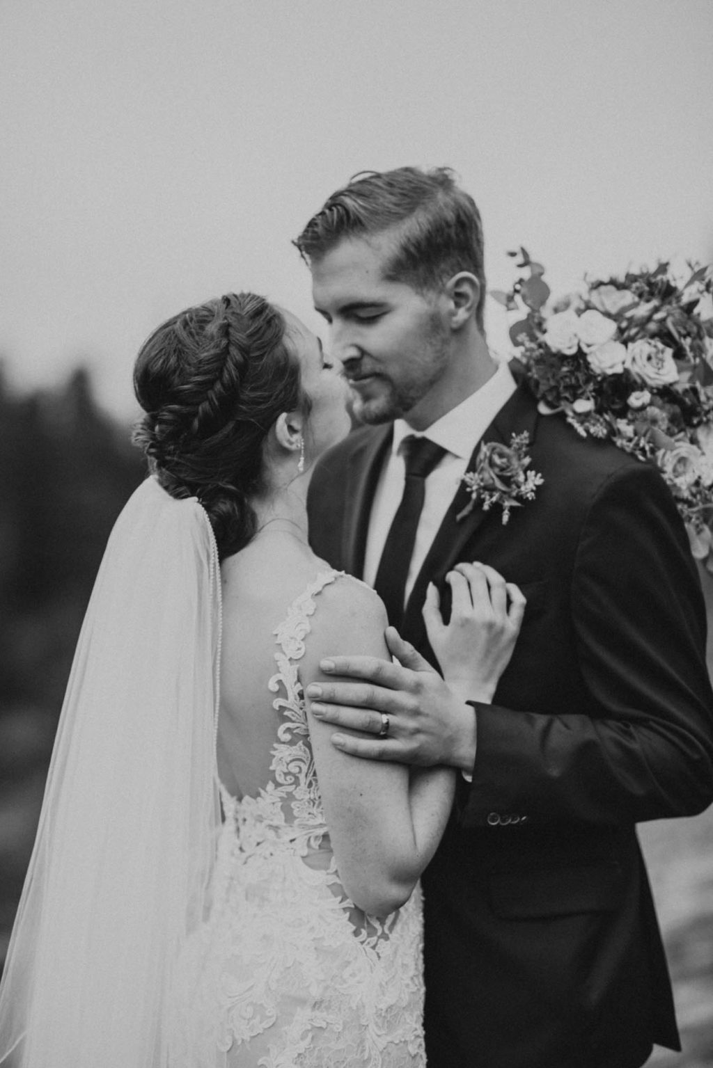 black and white of bride and groom almost kissing