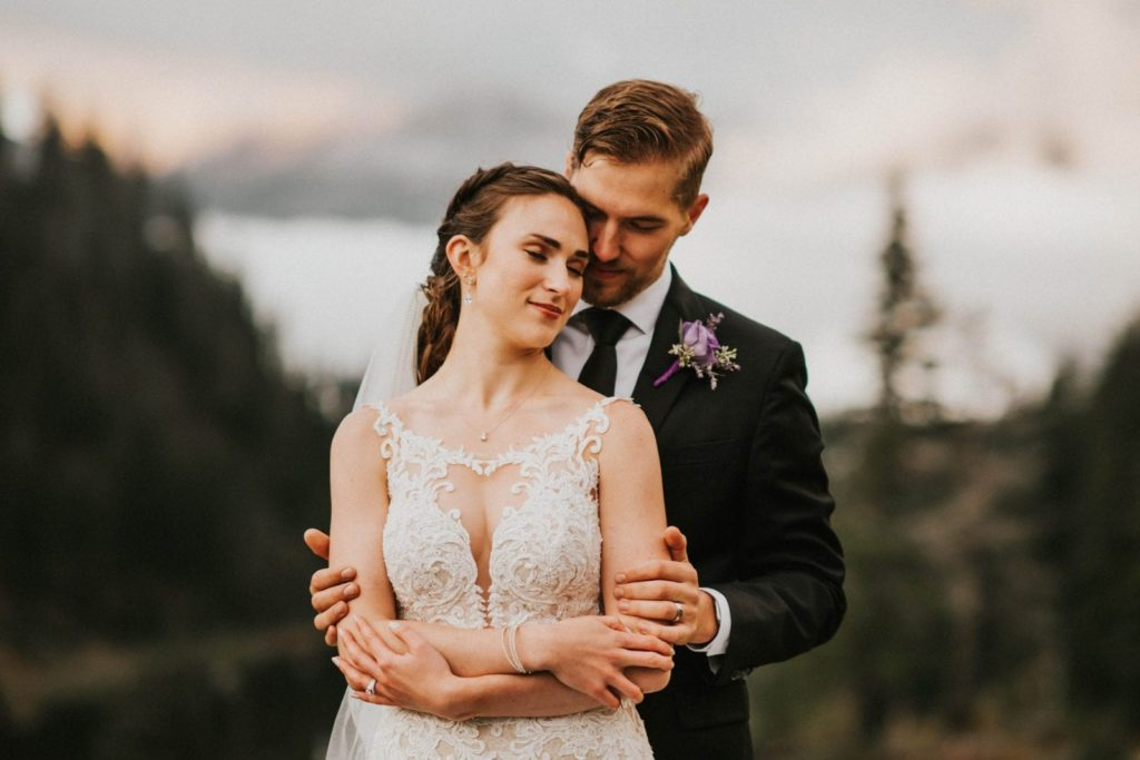 closeup of groom hugging bride from behind