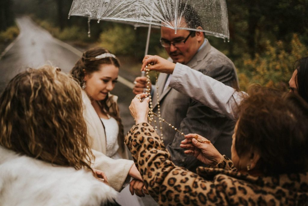 guests draping rosary beads over bride and groom