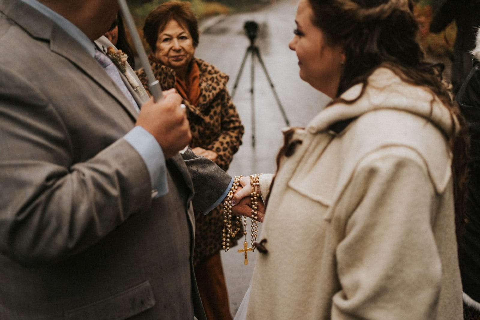 bride and groom holding rosary beads at ceremony