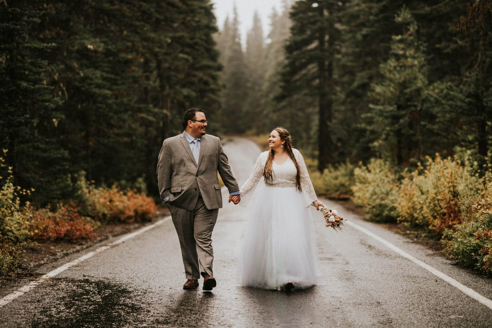 bride and groom posing in the road